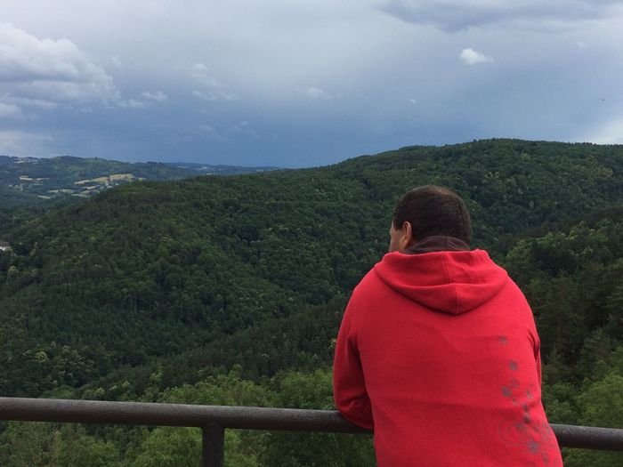 Man looking at mountains by railing against cloudy sky