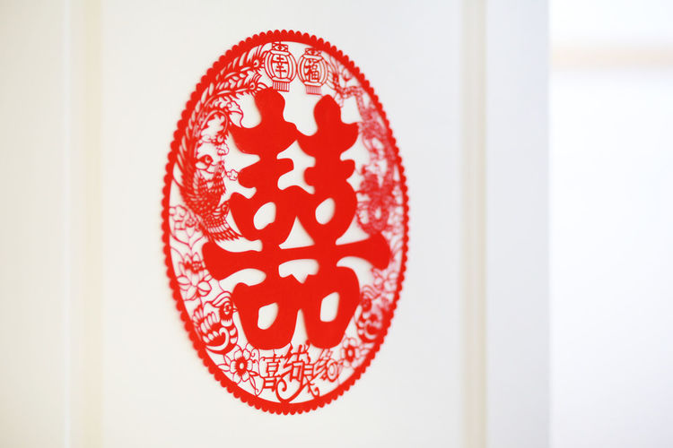 "Chinese symbol known as ""Double Happiness"" Red Close-up Indoors  No People Heart Shape Communication Pattern Focus On Foreground Creativity Text White Color Non-western Script Love Still Life Single Object Celebration Art And Craft Floral Pattern Wedding Double Happiness Paper Cutout Chinese Celebration Event Symbol"