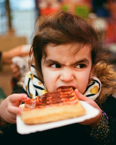 Close-up of girl looking away while eating waffle