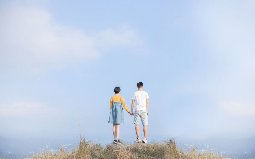Shorts Arm Around Looking At View Outdoors Adult People Positive Emotion Couple - Relationship Real People Nature Standing Day Lifestyles Love Leisure Activity Women Bonding Casual Clothing Full Length Men Two People Sky Togetherness Rear View Beauty In Nature Cloud - Sky