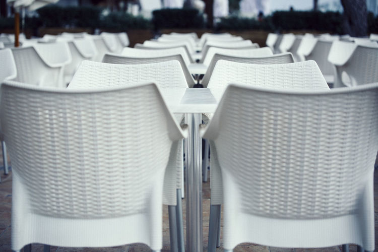 Aligned chairs and tables on an open air terrace in a holiday resort Aligned Bar Cafe Chair Close-up Day Empty Holiday Resort Holidays Hotel In A Row No People Open Air Outdoors Patio Resort Restaurant Seat Table Terrace