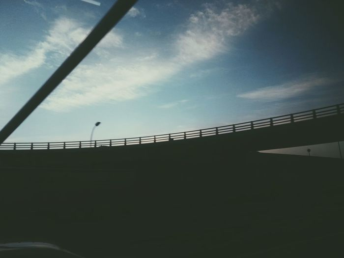 Low angle view of silhouette bridge against sky