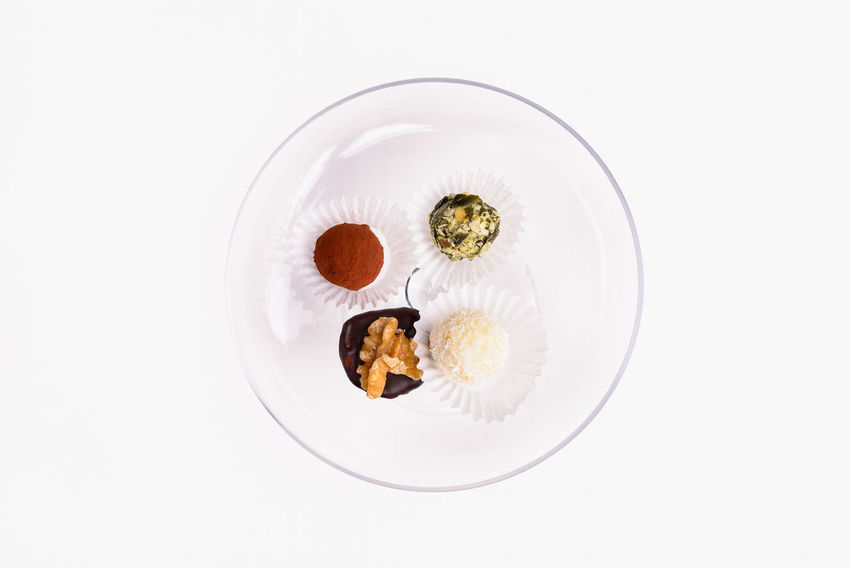 Four small candys or pralines on a glass plate Candy Chocolate Cocoa Coconut Dessert Dessert Food Food And Drink Isolated No People Petit Fours Pistachio Plate Pralines Studio Shot Walnut White Background