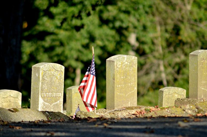 American Flag By Tombstones At Cemetery