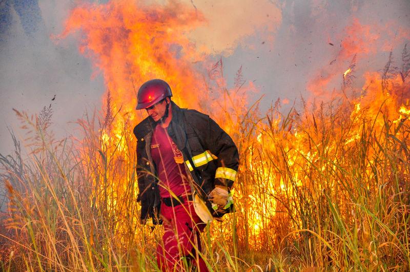Firefighter standing by fire on field