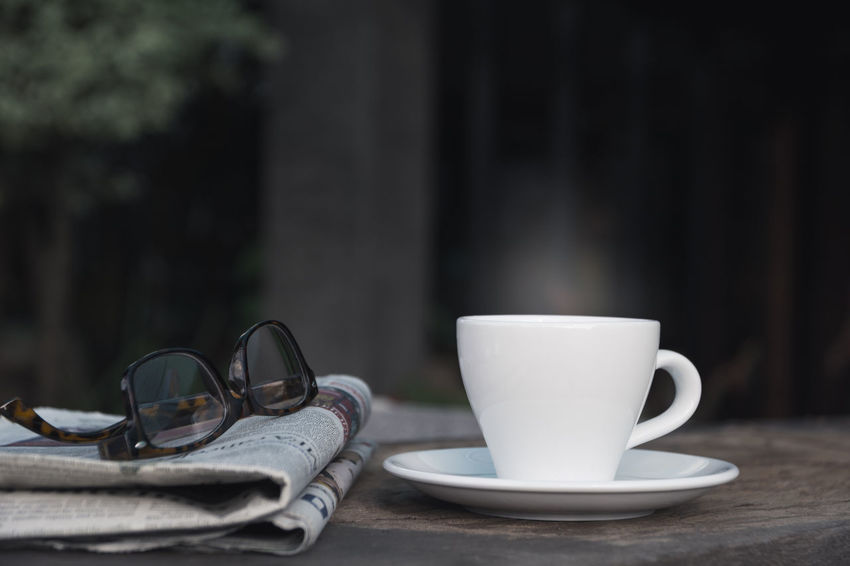 Glasses on a news paper with coffee cup on wooden table. Cup Mug Table Coffee Cup Coffee Drink Glasses Food And Drink Still Life Coffee - Drink No People Refreshment Eyeglasses  Close-up Crockery Focus On Foreground Day Absence Saucer Selective Focus Outdoors Personal Accessory Surface Level
