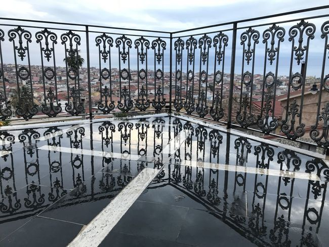 reflection of fence in the rain Architecture Bicycle Rack Bridge - Man Made Structure Built Structure City Day Graffiti In A Row Large Group Of Objects Metal No People Outdoors Railing Sky Wrought Iron