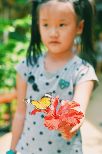 Close-up portrait of girl with butterfly on flower