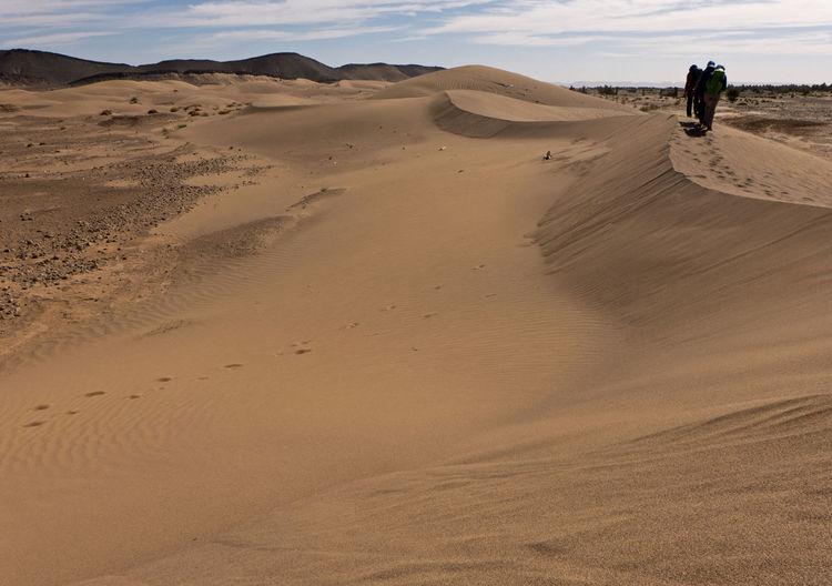 People walking on sand dune in desert