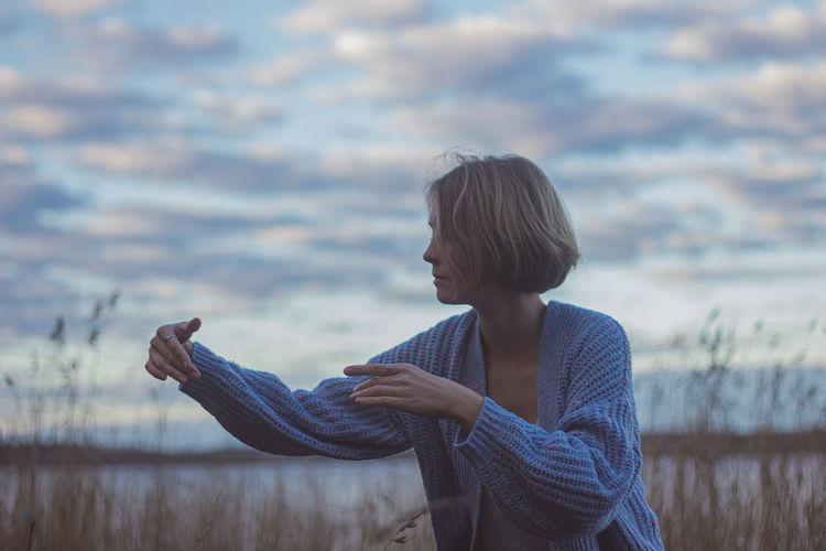 Woman dancing against cloudy sky