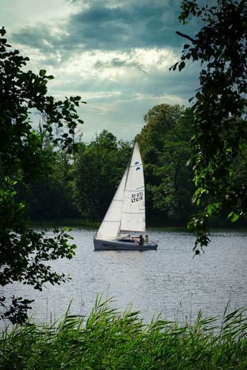 Sailboat on river against sky