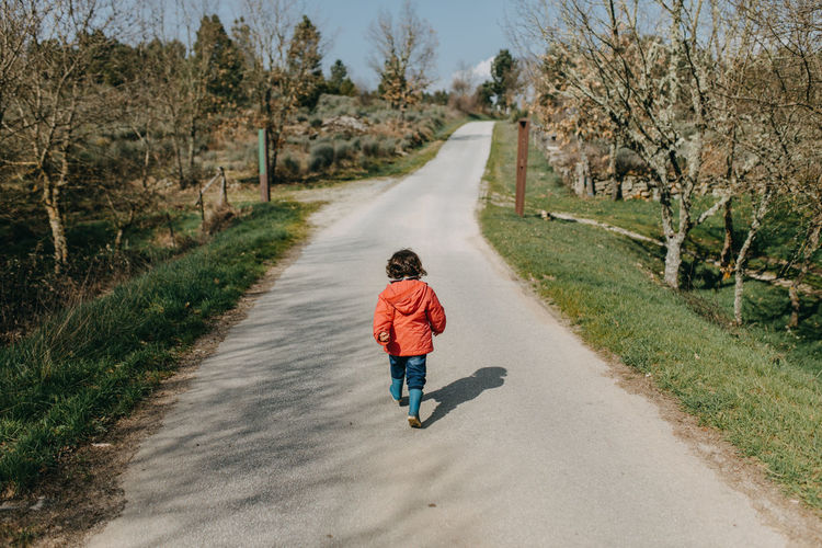 Rear view of boy walking on road