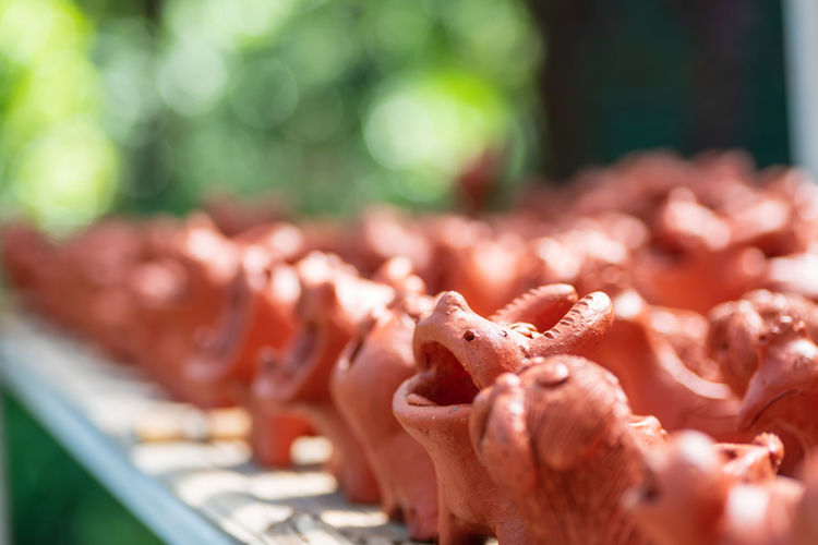 Row of smile animal clay dolls on rack in a clay shop Clay Doll Dolls Statue Beautiful Art Sculpture Happy Design Decoration Cute Handmade Smile Traditional Toy Craft Object Garden Animal Outdoor Pot Handicraft Row Rack Shop Close-up Selective Focus