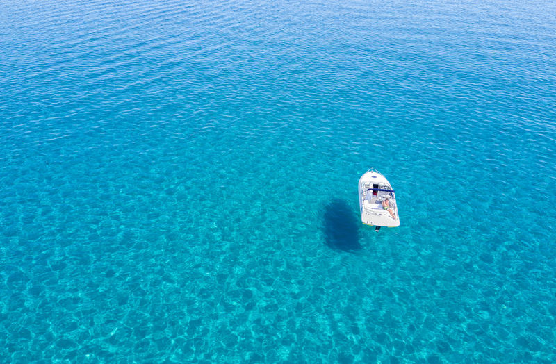 Man relaxing in his boat on the pristine waters of the Aegean sea in Greece Aerial Blue Boat Clear Clear Water Day Drone  Greece Greek High Angle View Holiday Mediterranean  Nature Nautical Vessel One Person Outdoors Paradise Relaxing Sea Swimming Tourist Travel Destinations Turquoise Vacation Water