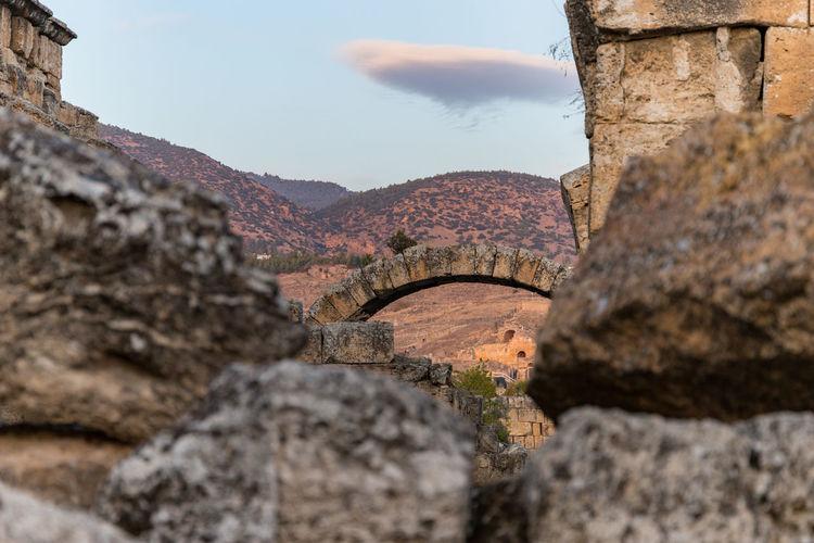 Stone wall by rocks against sky