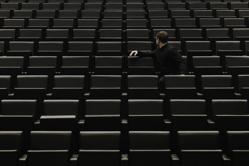 Man sitting on chair in auditorium
