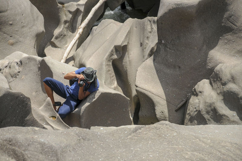 High angle view of man photographing while sitting on rock
