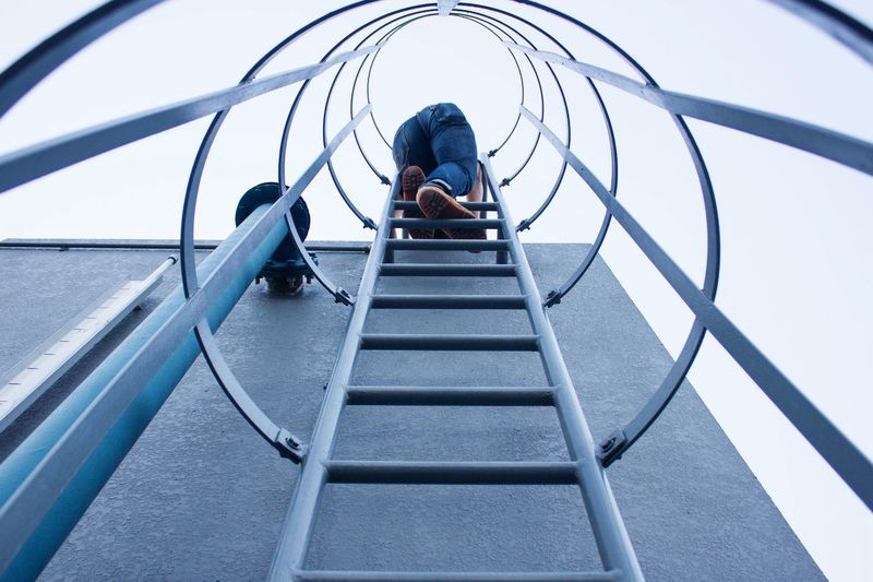 Low Angle View Of Man On Emergency Ladder