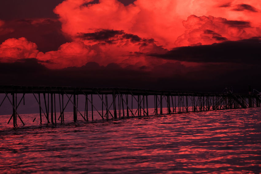 Pier at thunderstorm Danger Zone Pier Stormy Weather Thunderstorms Dramatic Sky Reflecting Water Reflection Sundown Landscape Sunset Wild Nature Magic