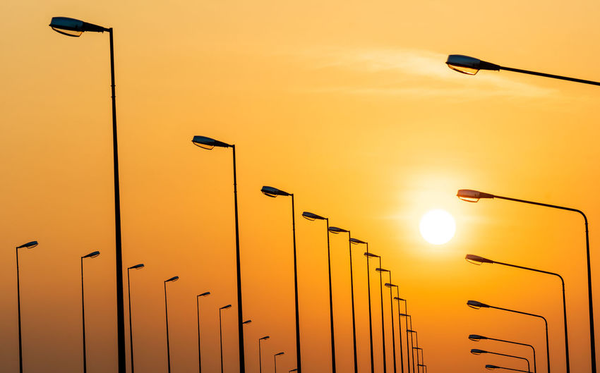 Low angle view of street lights against orange sky