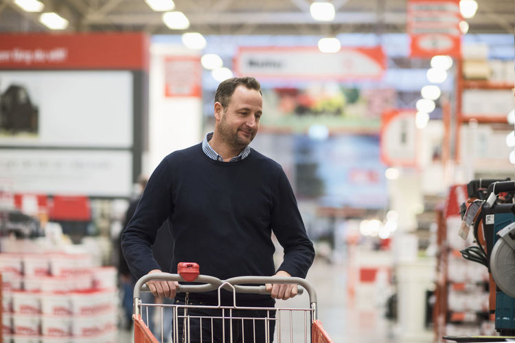 Man smiling while looking away at store