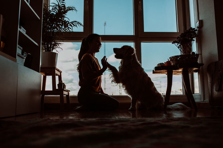 Side view of woman playing with dog at home