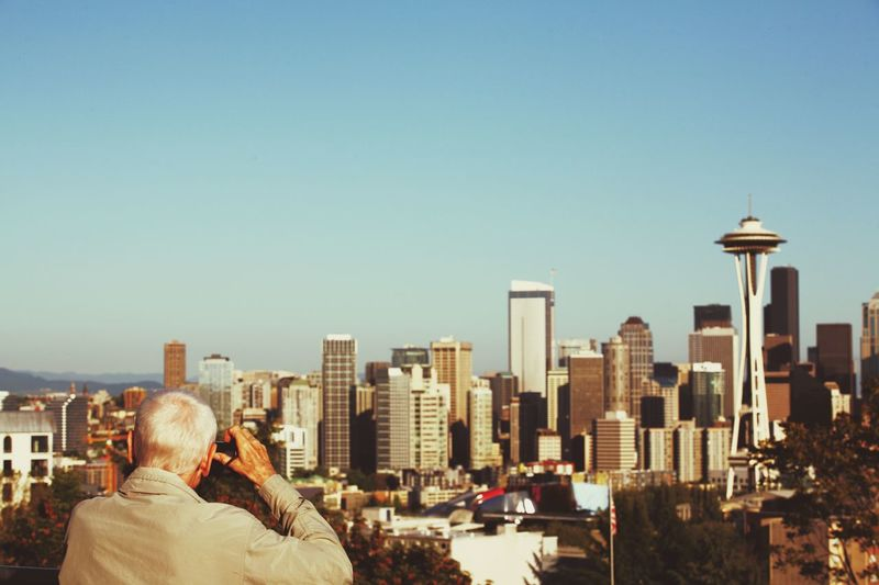 Rear View Of Man Photographing Space Needle Amidst Buildings In City Against Clear Sky On Sunny Day