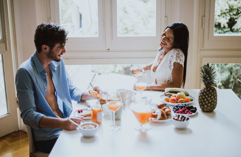 Smiling couple talking while having breakfast at dining table
