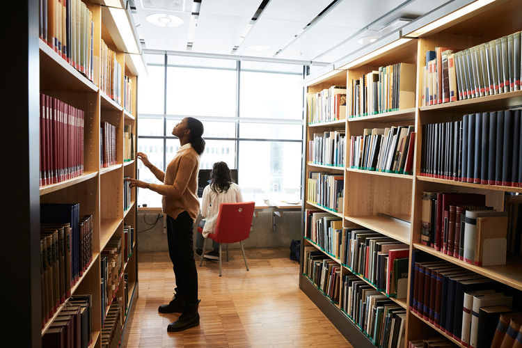 Woman searching book in library
