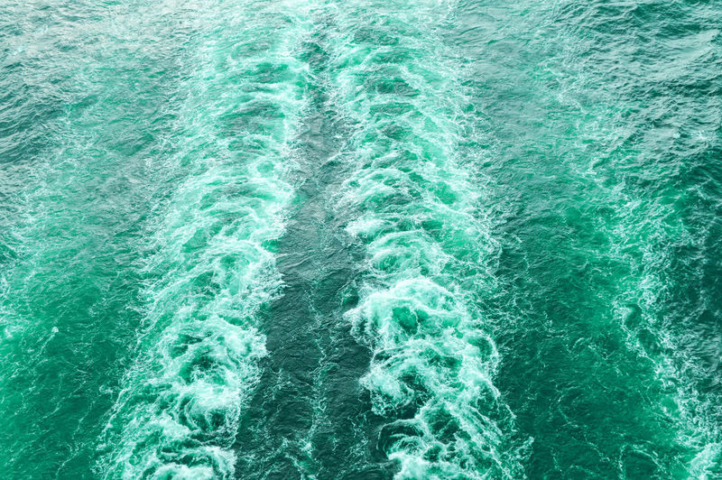 Stormy foam and a ship's track on the turquoise sea water.
