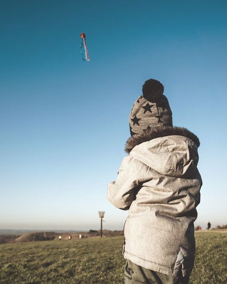 Rear view of boy wearing warm clothing while flying kite against clear sky
