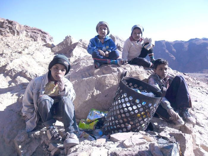 Friends sitting on rock formations amidst garbage can