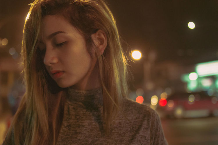 Young woman in illuminated city at night