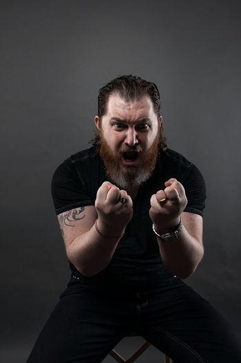 Angry Mid Adult Man Clenching Fist While Sitting Against Black Background