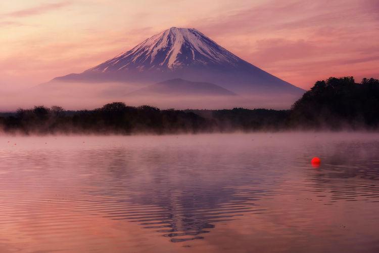 Mountain fuji with reflection and mist on water of lake shoji shojiko at dawn with twilight sky,