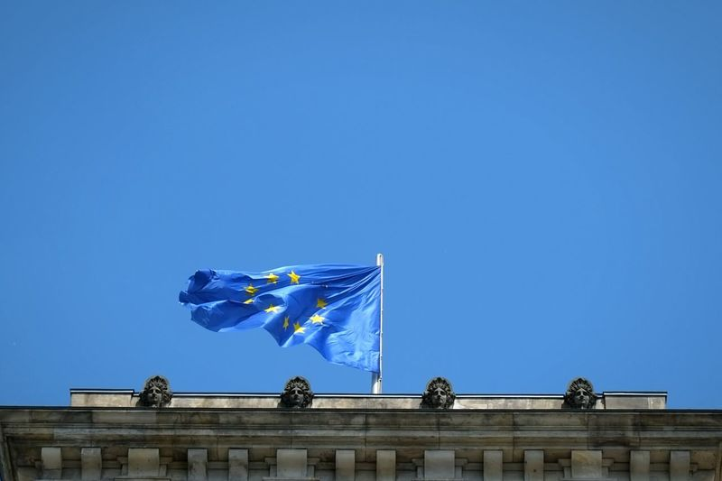 Low angle view of european union flag on building against clear sky