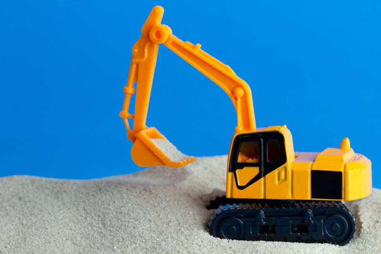 Yellow toy backhoe is digging sand on the blue of construction. Automobile Construction Industry Land Life Transport Transportation Wheel Artificial Backhoe Blue Closeup Colorful Concept Dump Equipment Industry Model Plastic Sand Small Still Life Toy Vehicle Yellow
