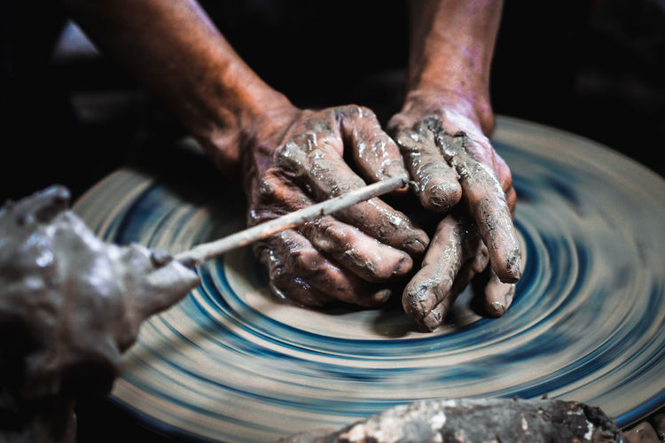 Cropped hands of man working on pottery wheel