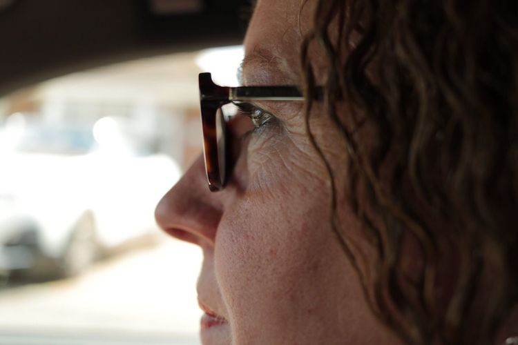 Side view of mature woman wearing eyeglasses in car