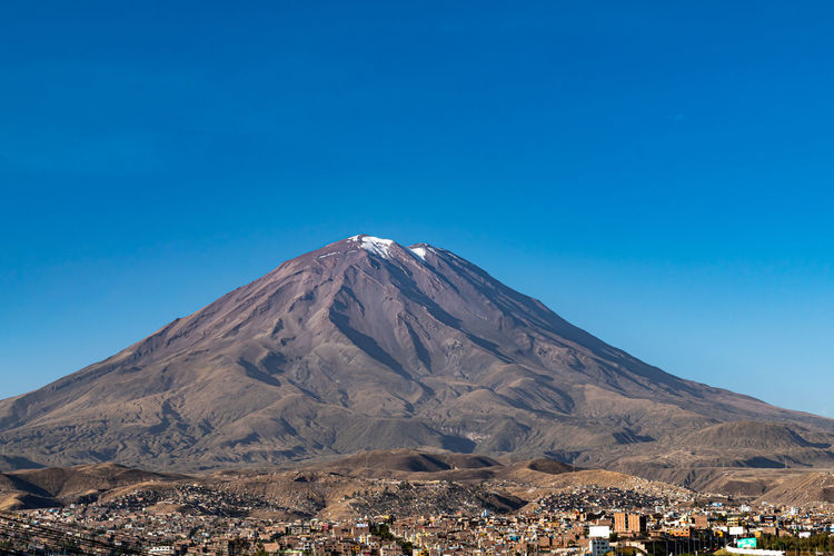 Scenic view of the volcano el misti looming over the city of arequipa, peru against blue sky