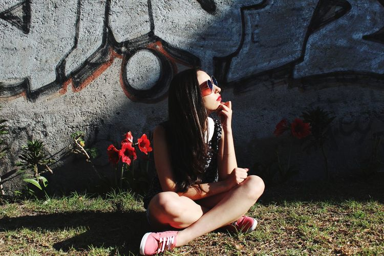 Thoughtful young woman sitting on field against graffiti wall