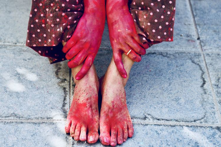 Low section of messy woman sitting on footpath during holi