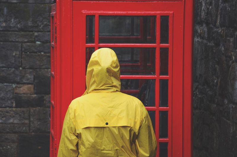 Rear view of person standing against red telephone booth