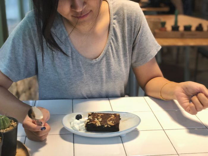 Midsection of woman having chocolate cake at table in restaurant