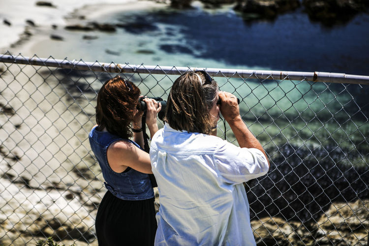 17 Mile Drive Balance Carefree Casual Clothing Chainlink Fence Childhood Famous Place Fence Focus On Foreground Front View Fun Getting Away From It All Leisure Activity Lifestyles Mother And Daughter Portrait Protection Real People Safety Standing Three Quarter Length Tourist Watching Young Adult