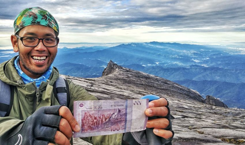 Portrait Of Smiling Man Holding Paper Currency Against Mountains