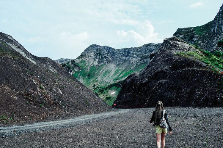 Rear view of woman walking on road against mountain range