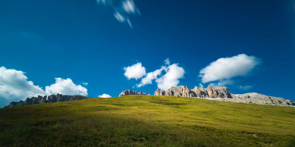 View from Passo Pordoi to the Piz Boe mountain and a large meadow underneath Beauty In Nature Blue Cloud Cloud - Sky Day Dolomites Dolomiti Exposure Grassy Green Color Italy Landscape Long Low Angle View Motion Mountain Mountain Range Movement Nature Outdoors Remote Rock Formation Scenics Tranquility
