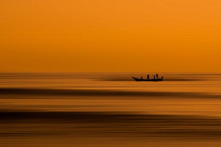 Silhouette boat on sea against orange sky