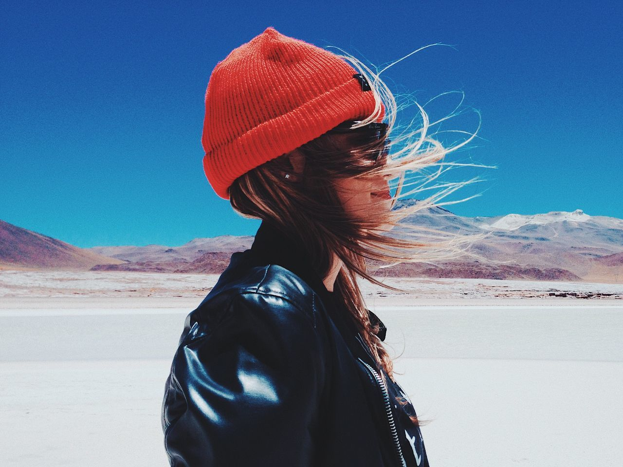 Side View Of Woman With Tousled Hair Standing In Desert Against Blue Sky